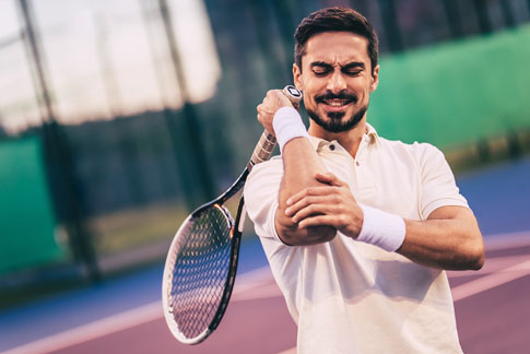 Man playing tennis with a hurt elbow